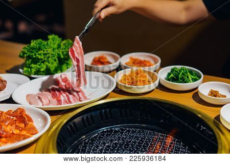 Japanese Or Korean Yakiniku Style Restaurant. Hands Women Having Roasted Sliced Of Beef In Japanese
