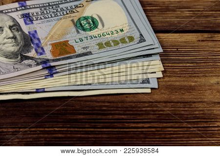 Stack Of One Hundred Dollars Bills On Wooden Desk