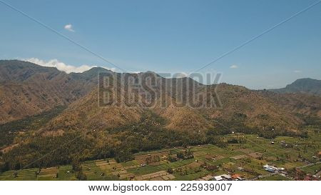 Village In The Mountains With Farmlands, Fields With Crops, Trees. Aerial View Of Mountains Are Cove