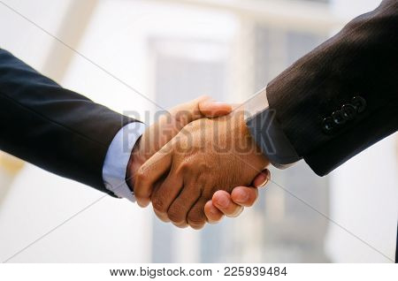 Welcome. Deal. Close Up Of Business Man In Suit Handshake After Finishing Up A Business Meeting In T
