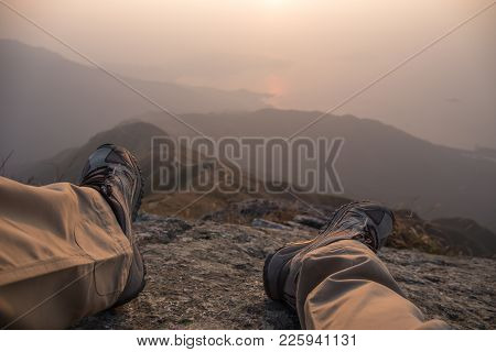Feet And Leg Of Hiker Sit On Peak With Hiking Trail And Mountain Range Background With Fog At Sunris