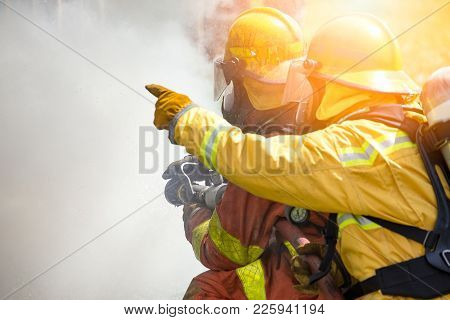 Close Up Action Of Two Firefighters Water Spray By High Pressure Nozzle To Fire Surround By Smoke Wi