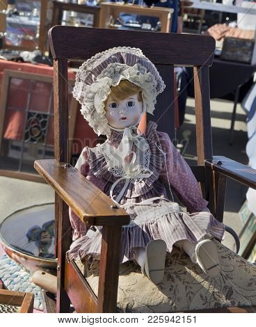 Vintage Doll Sitting In Old Chair At Flea Market.