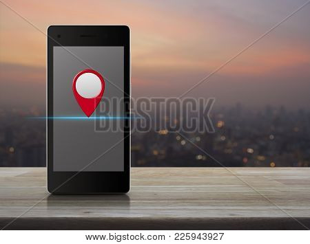 Map Pin Location Button On Modern Smart Phone Screen On Wooden Table Over Blur Of Cityscape On Warm
