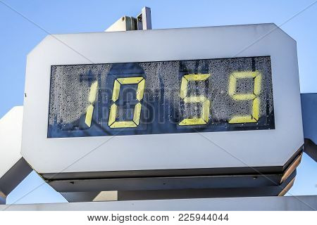 Digital Outdoor Clock Is Showing 10:59 In Yellow Numbers