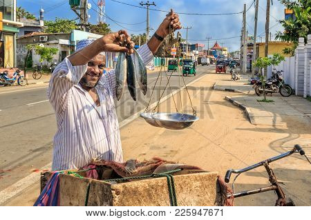 Kalpitiya, Sri Lanka - January 3, 2018. Portrait Of A Street Fish Seller With Hand Scales And A Bicy