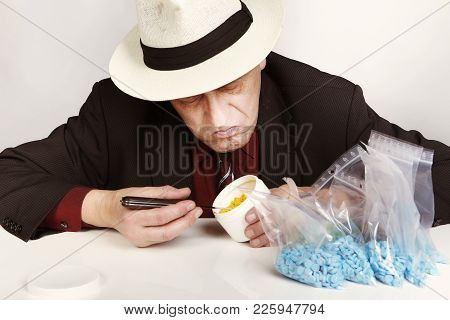 Older Dealer Of Mdma Drugs Counting And Checking Lot Of Pills