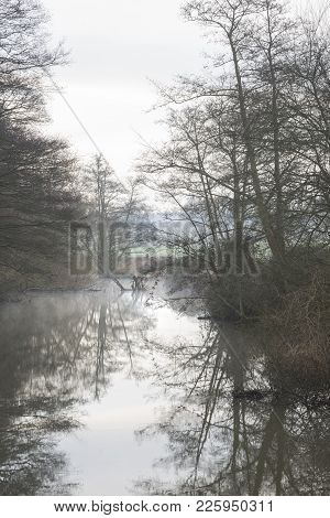Low Hanging Misty Morning Landscape Over Calm Stream In English Countryside Landscape Image