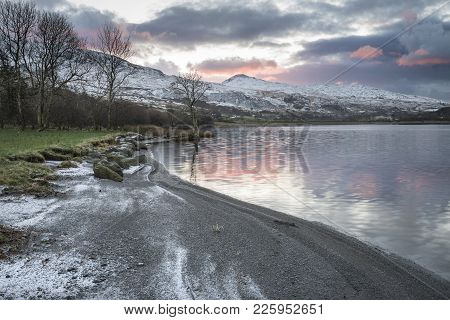 Stunning Sunrise Landscape Image In Winter Of Llyn Cwellyn In Snowdonia National Park With Snow Capp
