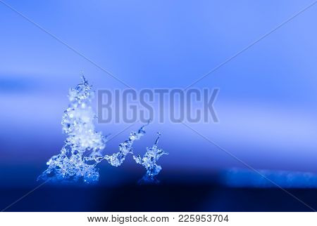 Art Photo Of Frozen Water, Crystals Of Snow And Ice Close-up On Blue Blurred Background