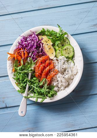 Smoked Salmon, Rice, Vegetables Buddha Power Bowl On Blue Background, Top View. Red Cabbage, Carrots