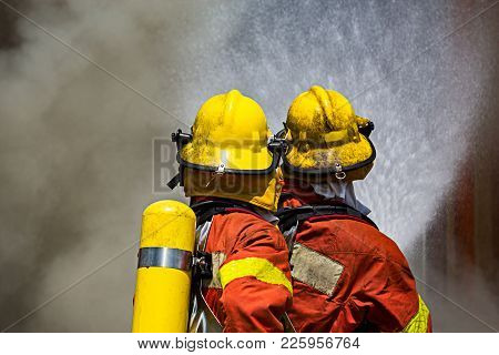 Two Firefighters Water Spray By Fire Hose Surround With Dark Smoke