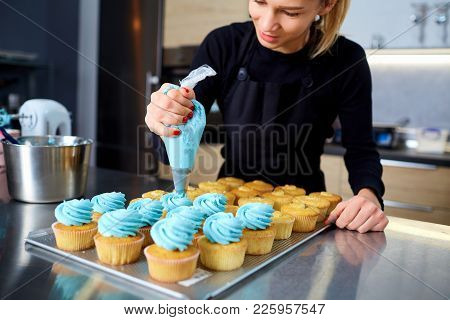 The Confectioner With A Pipping Bag Of Cream In His Hands Decoretion Cupcake On The Table In The Kit
