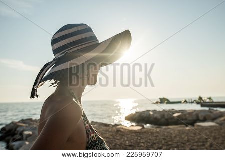 Rear View Of A Relaxed Woman Wearing A Striped Straw Hat At The Beach At Sunset During Summer Vacati