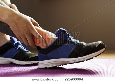 Young Woman Suffering From An Ankle Injury While Exercising. Sport Exercise Injuries Concept.