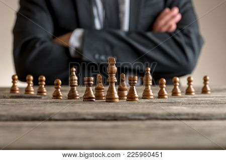 Man Wearing Suit Sitting With Folded Arms In Front Of Dark Chess Pieces At Table .