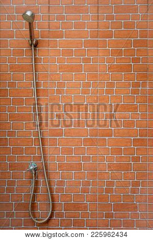 Silver Shower Head Set Up On Red Brick Wall.