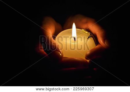 Burning Candle In The Hands Of A Praying Girl On A Black Background