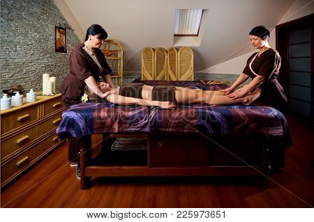 Massage In Four Hands In The Spa Salon. Two Massage Therapist Make Massage For A Woman.