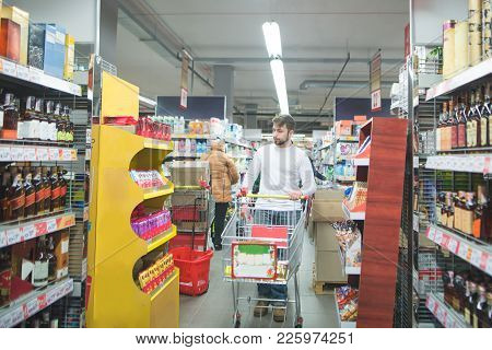 A Man With A Shopping Cart Walks In The Alcohol Department Of The Supermarket And Chooses Wine