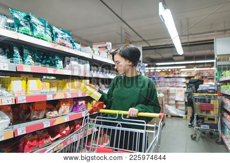 Beautiful Young Girl With A Shopping Carts Chooses Shopping At A Supermarket. The Girl Looks At The