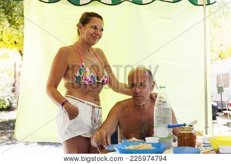 Smiling Mature Man Preparing Lunch With His Wife