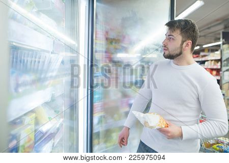 Portrait Of A Man Near A Refrigerator In A Supermarket With Frozen Foods In His Hands.
