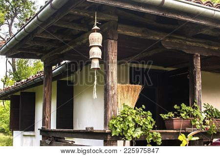 Country House Facade With Ceramic Clay Pottery Decorative Garden Wind Chime Bells On A Rope Under Wo