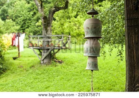 Countryhouse Garden View With Ceramic Clay Pottery Decorative Garden Wind Chime Bells On A Rope In F