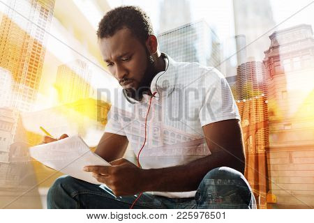 Complicated task. Young clever diligent student looking at the tasks in his hand and feeling worried while trying to cope with them poster