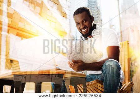 Positive Smile. Positive Optimistic Handsome Student Sitting At The Little Table In A Lovely Cafe Ou