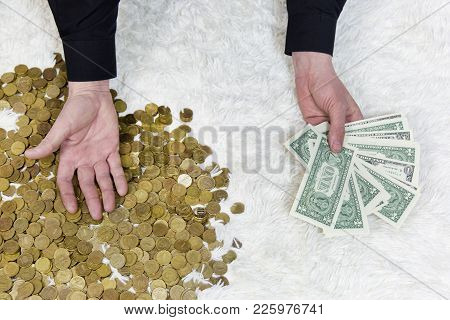 A Man In One Hand Holds A Bundle Of Paper Dollars, And Put His Other Hand On A Pile Of Coins.