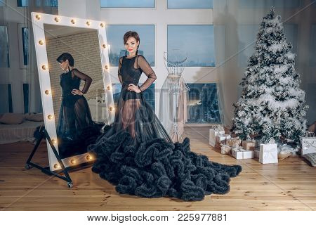Elegant Young Woman In Black Evening Dress Posing In Vintage Interior Near The Mirror. Fashion Shot.