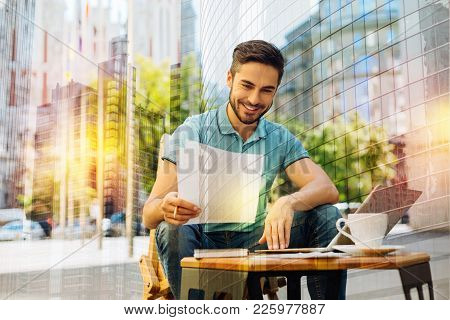 Ready Pages. Clever Enthusiastic Cheerful Student Sitting At The Table With A Modern Laptop On It An