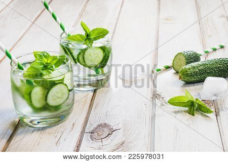 Summer Refreshing Detox Cocktail. Water With Cucumber, Mint And Ice In Glass On A White Wooden Backg