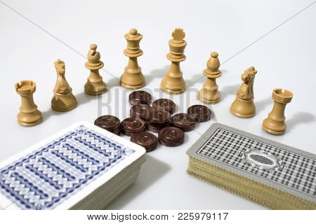 Chess Pieces And Cards Composition In A White Background