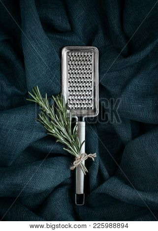 Kitchen Accessory. Metal Cheese Grater With Rosemary On Textile Background.