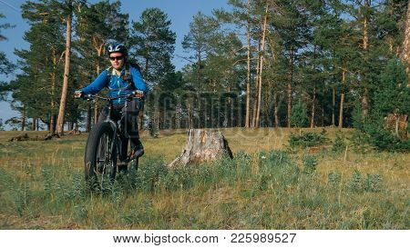 Fat Bike Also Called Fatbike Or Fat-tire Bike In Summer Riding In The Forest. The Guy Rides A Bicycl