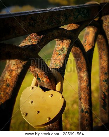 Yellow Lock In Form Of Heart Hangs On Old Rusty Fence