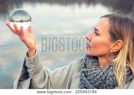 Portrait Of Blond Woman In Front Of Lake Holding Up A Glass Ball