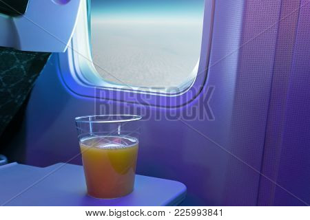 A Cup Of Orange Juice On Tray At Cabin Seat Of An Aircraft.