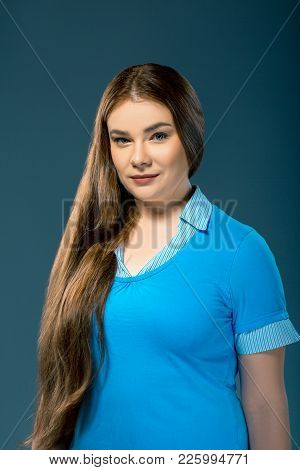 Attractive Plus-sized Woman Wearing Blue Blouse In Studio Setting. Girl With Long Hair Over Blue Bac
