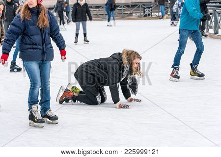 Stockholm, Sweden - February 3, 2018: Side View Of A Woman Lying On Her Knees On The Ice When Skatin