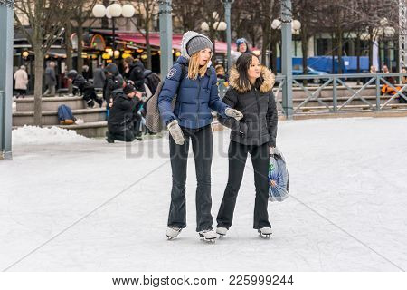 Stockholm, Sweden - February 3, 2018: Front View Of Two Girls Skating At A Public Ice Skating Rink O