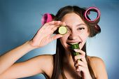happy woman with curlers on her head eating cucumber poster