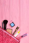 Cosmetics bag with makeup products, top view. Cosmetics and makeup tools in pink toiletry bag, copy space. Feminine makeup background. poster