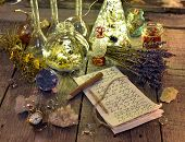 Witch manuscript with writings, magic bottles, crystals and lavender flowers on planks. Occult, esoteric, divination and wicca concept. Halloween background. No foreign text, all symbols on pages are fantasy, imaginary one poster