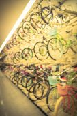 Blur wide selection of bicycles at sporting goods chain store in Houston, Texas, US. Various modern road, touring, cyclocross, mountain, commuter bikes on three tier sloping display rack. Vintage tone poster