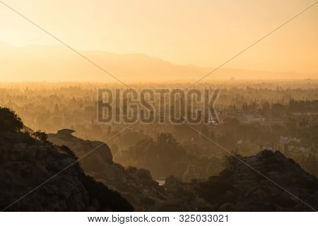 Hazy morning sunshine above West San Fernando Valley neighborhoods in the city of Los Angeles, California.  The San Gabriel Mountains are in the background.