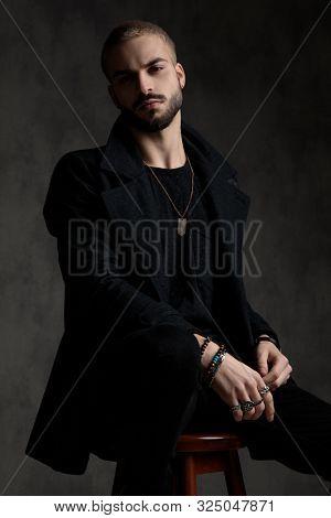 arrogant fashion model wearing black longcoat, rings, bracelets and necklace, sitting on grey background in studio